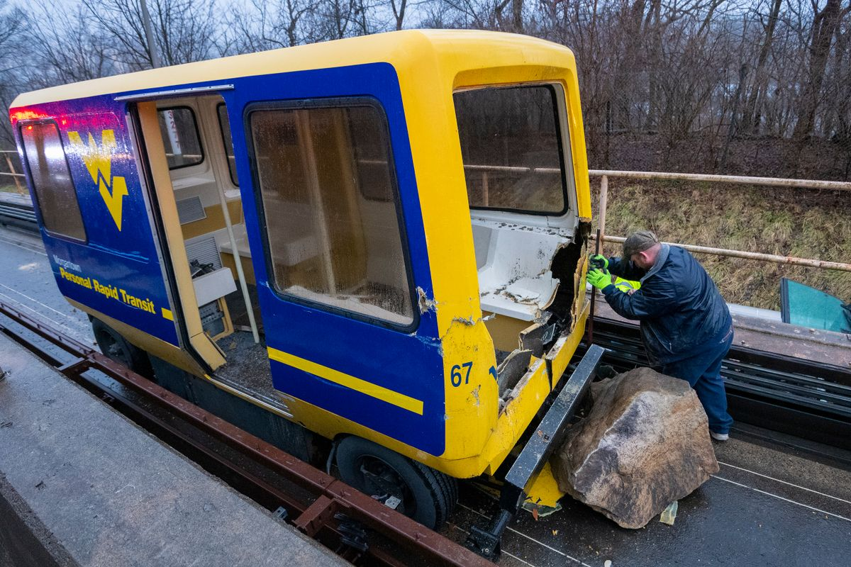 WVU personnel work on the PRT tracks after a rock slide Monday, Feb. 10, 2020. To safely remove people from the PRT vehicle, emergency officials needed to remove a large portion of the vehicle.