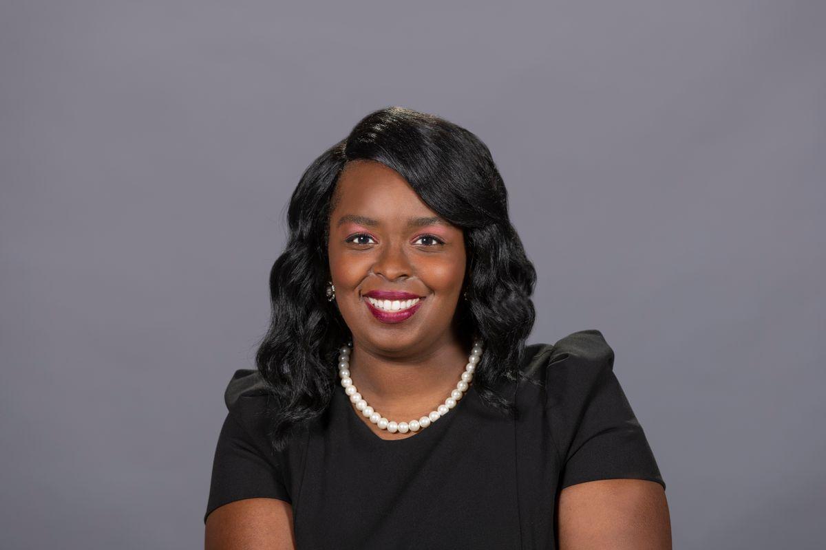 black woman smiles wearing a black dress