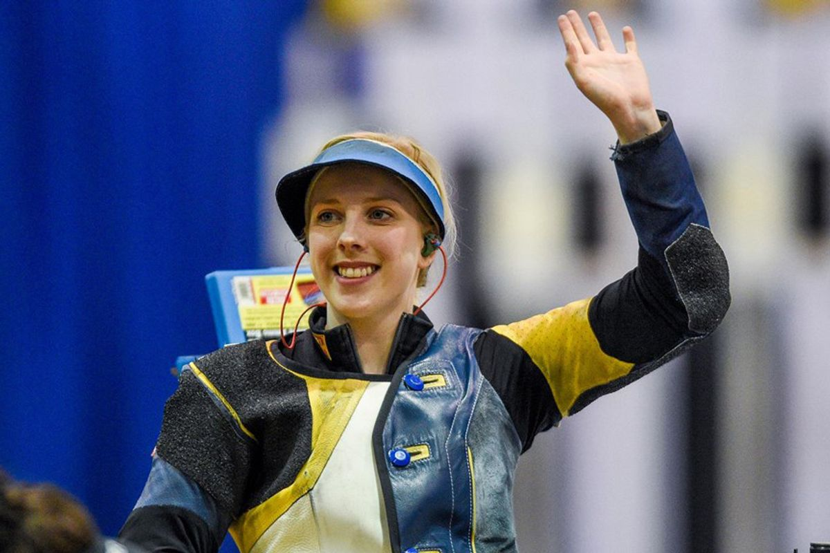 Ginny Thrasher smiles and raises her left hand to wave to the crowd after a win.