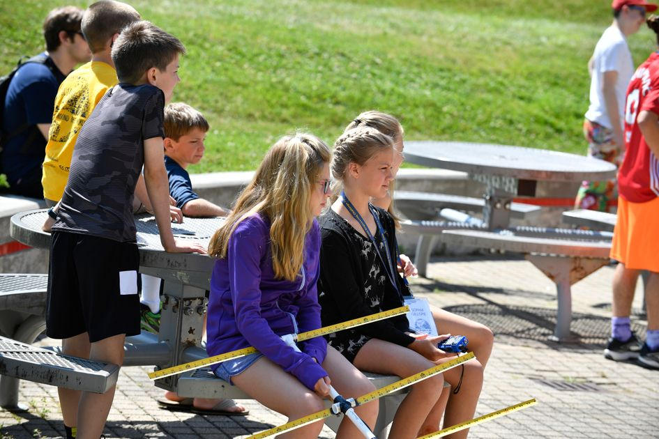 Middle school students sit outside at picnic tables