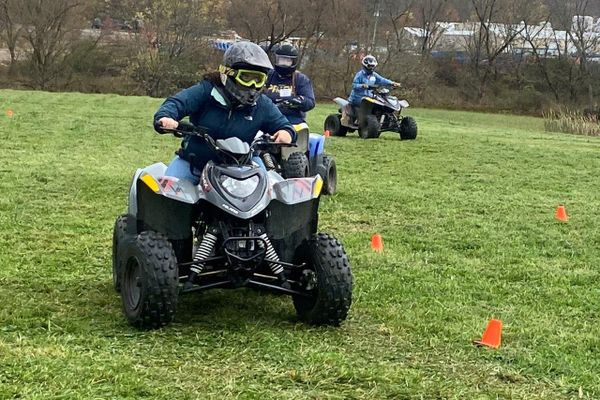 person on ATV driving around orange flags in green grass