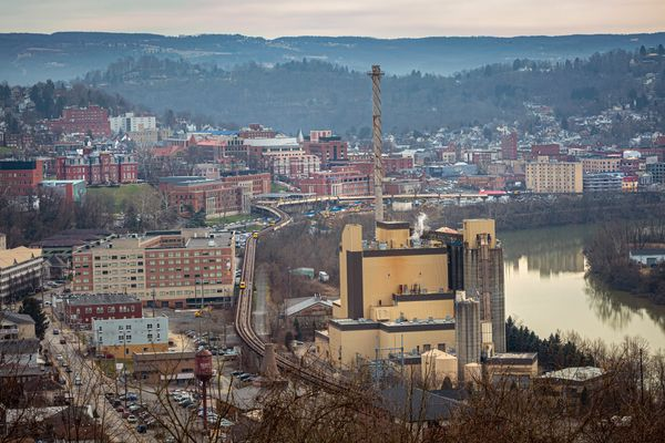 view of power plant by a river, city in background