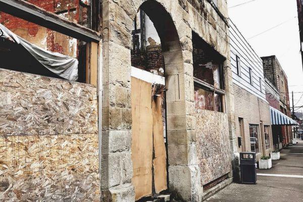 stone building with arched doorway, broken window