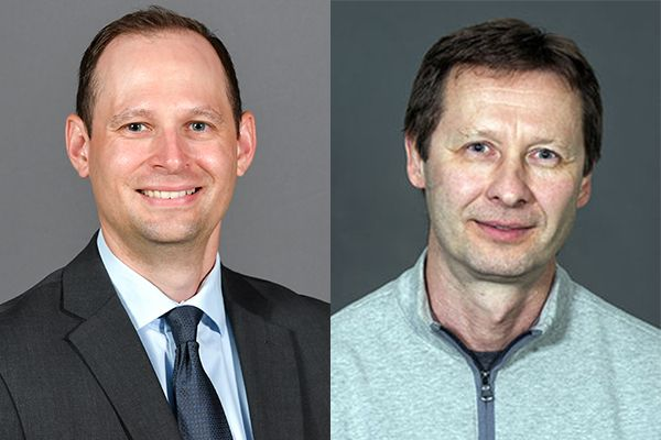 two men's headshots next to one another, man on right wearing suit and man on left wearing a sweater on grey background
