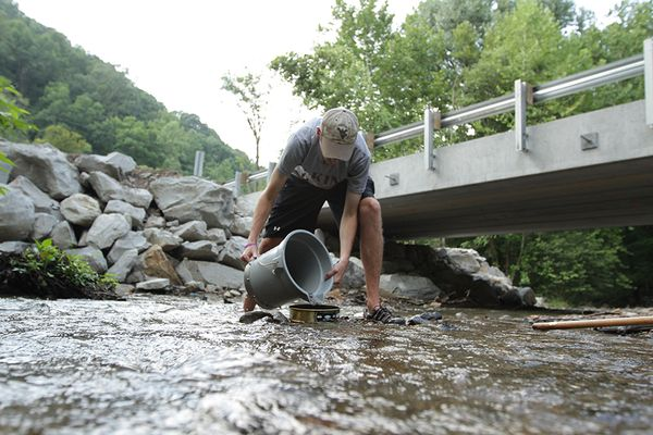 Man filling up bucket of water next to a bridge