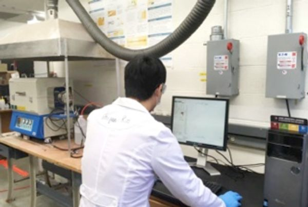 Man in a lab coat looks at a computer