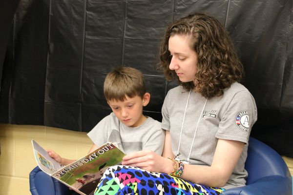 A young woman in a gray t-shirt reads to a boy