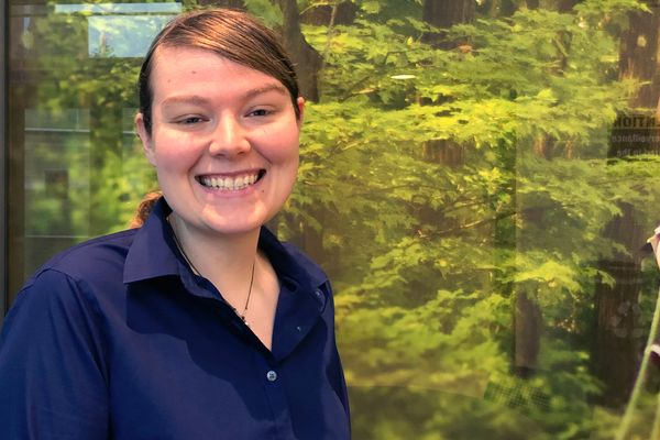 smiling woman stand in front of backdrop of green trees