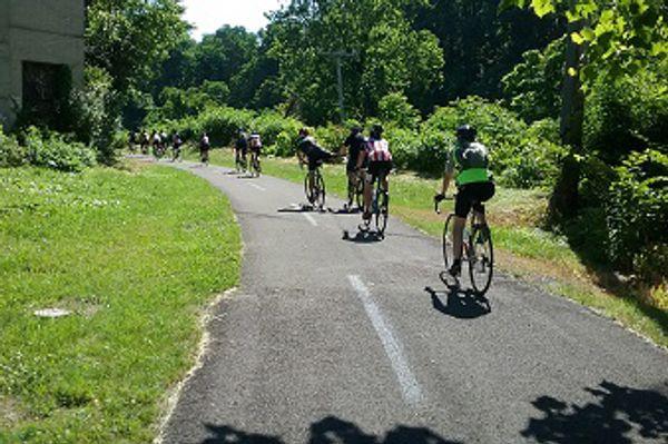 A line of cyclists on a paved trail
