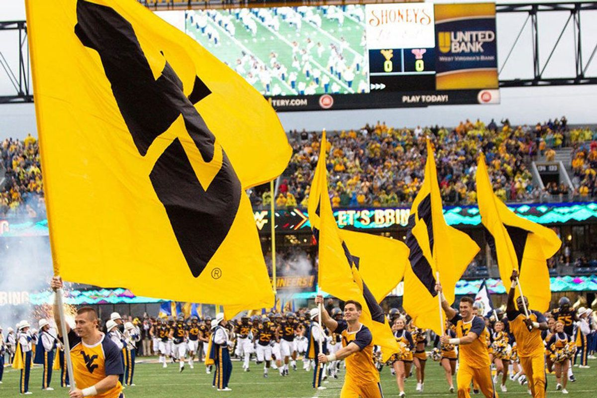 WVU cheerleaders carry WVU flags on Mountaineer Field during a football game.