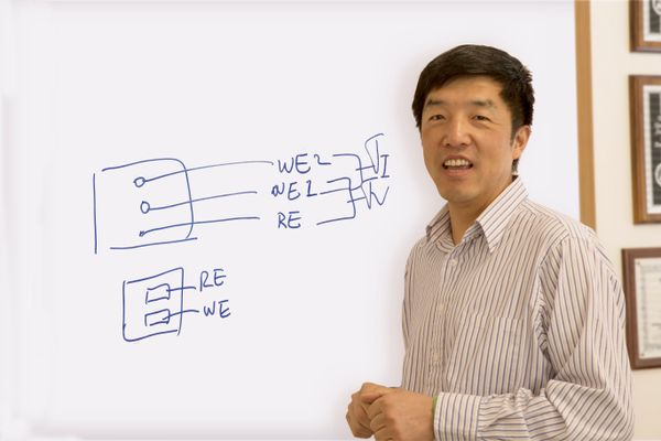 WVU researcher Xingbo Liu standing in front of a white board with equations on it.