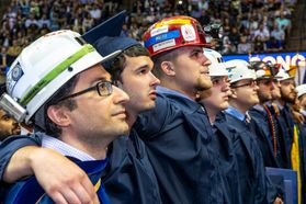 men in hard hats stand with arms around each others' shoulders