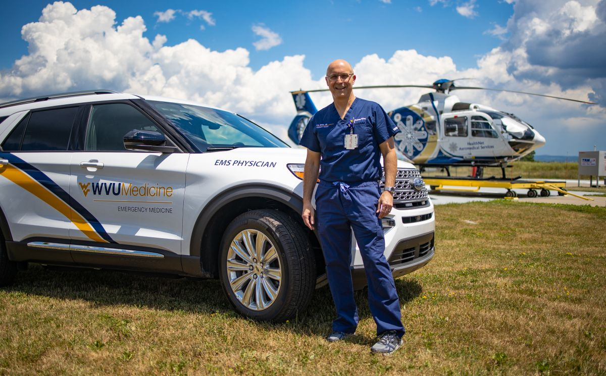 bald man in scrubs in front of car