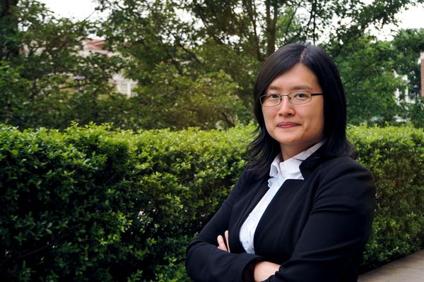 Woman with black hair wearing a black blazer and glasses with her arms crossed.