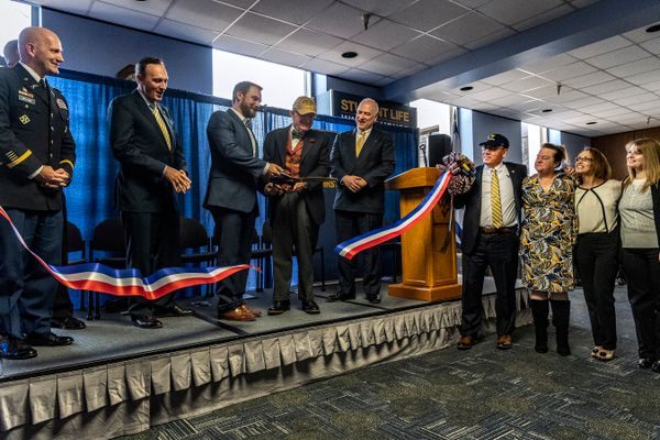 Platform party members watch as L to R, Ed E. Olesh, president, Veterans of WVU, and WVU President E. Gordon Gee cut the ribbon opening the new WVU Veteran and Military Family Support Headquarters December 7, 2018. Photo Greg Ellis