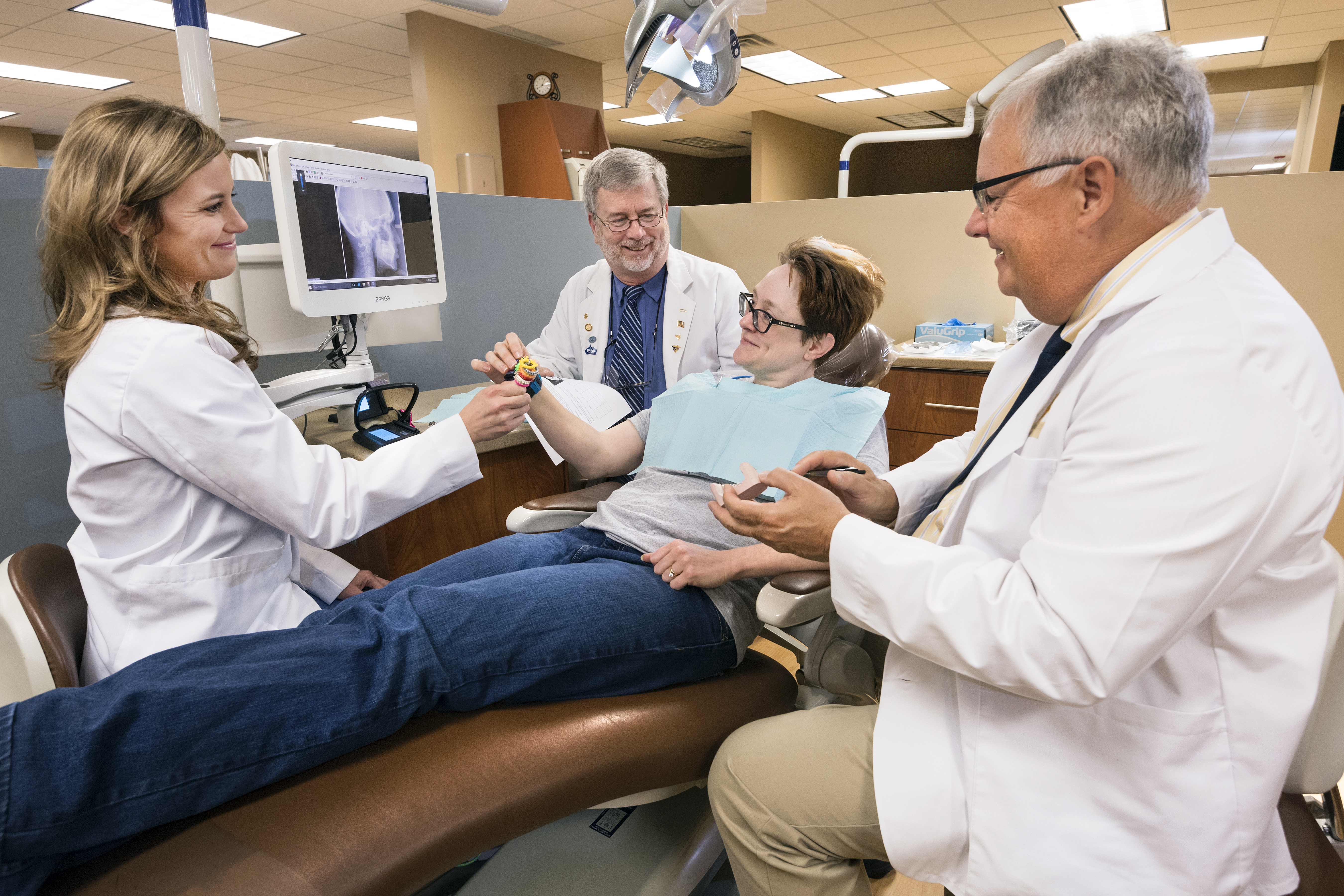 Dental professionals sitting with patient