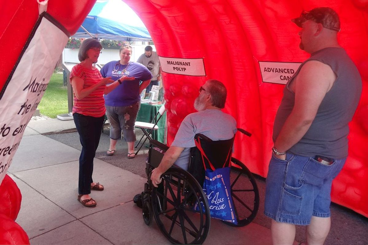 man in wheelchair speaks with woman holding clipboard, man in foreground