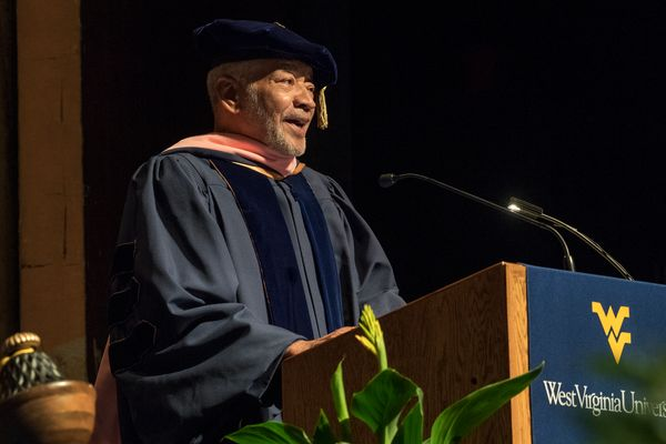 man in commencement garments speaks at podium