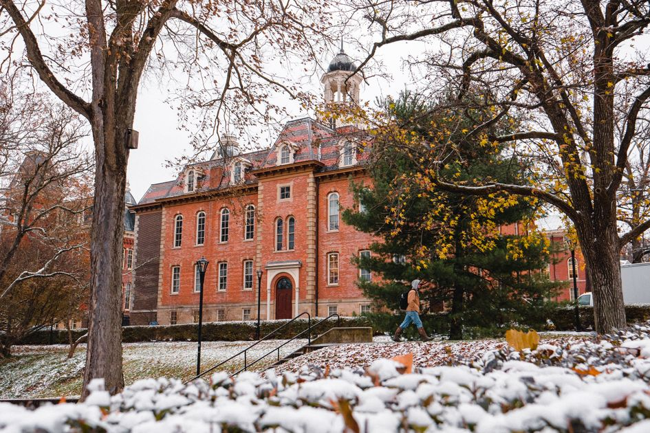 WVU student walks by Martin Hall on a snowy day.