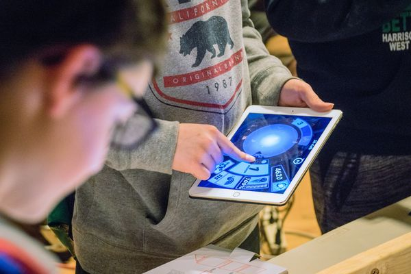 Boy with glasses looks at a computer tablet