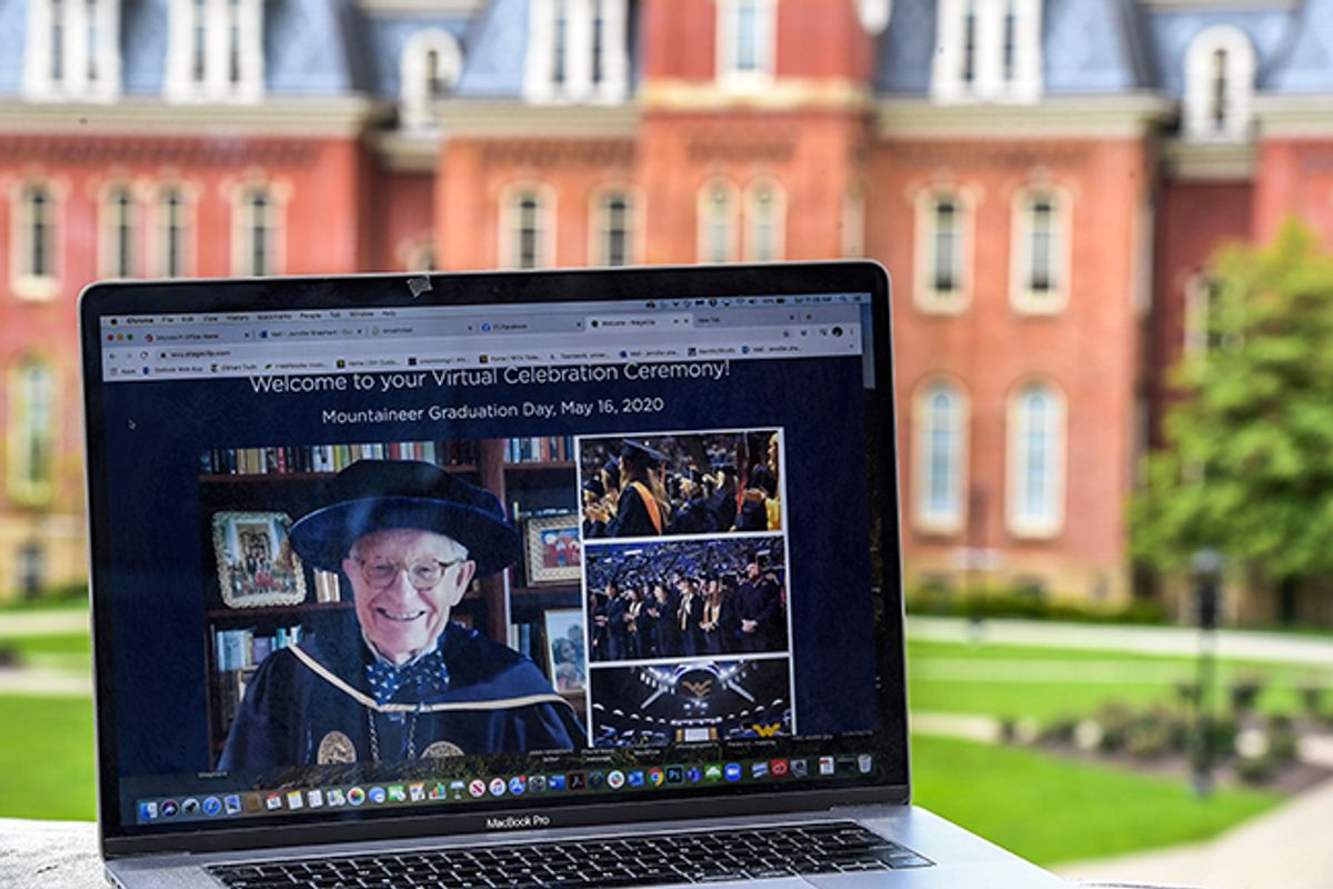laptop computer screen with man in graduation regalia in front of large brick building