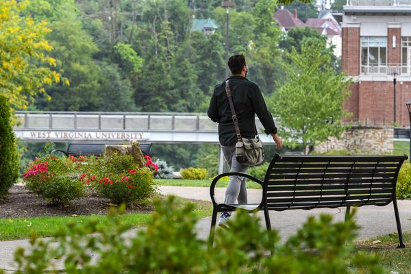 a person walks past a bench, footbridge in background, green trees, large brick building in distance