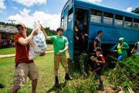 Young people unload items form a bus