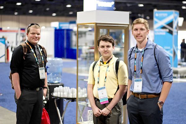 Three male students standing at the SAMPE conference