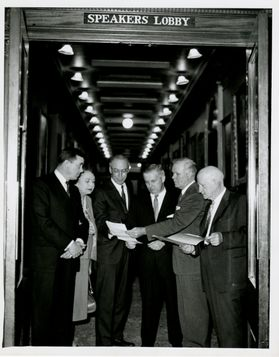 Group of people gather around a document in black and white photo.