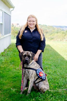woman in dark blue shirt with brindle dog