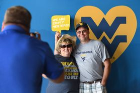 Two parents pose for a man in a blue shirt taking a picture of them in front of a blue and gold WV backdrop.