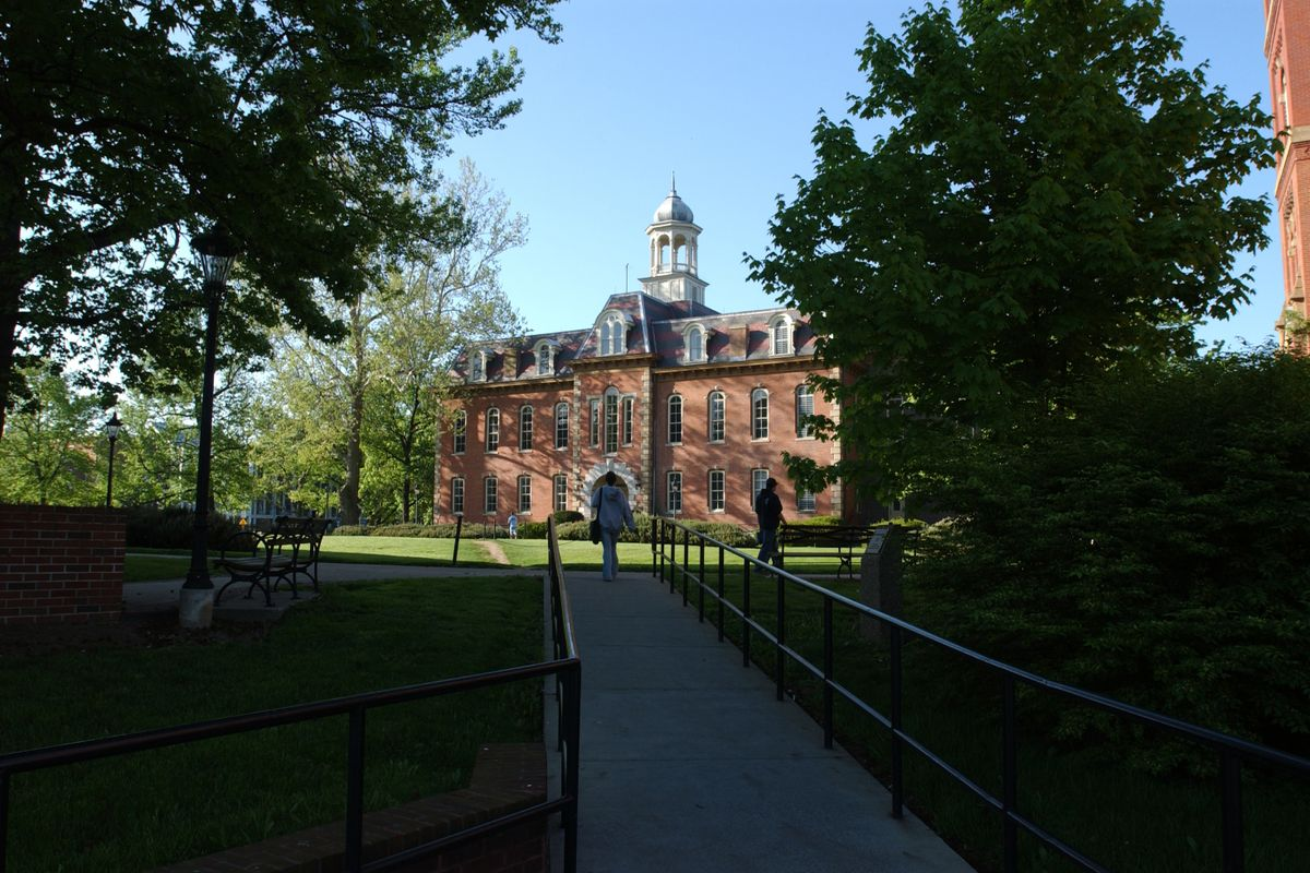Photo of a red brick building at the end of a walkway, surrounded by shadowed trees, green grass and blue sky