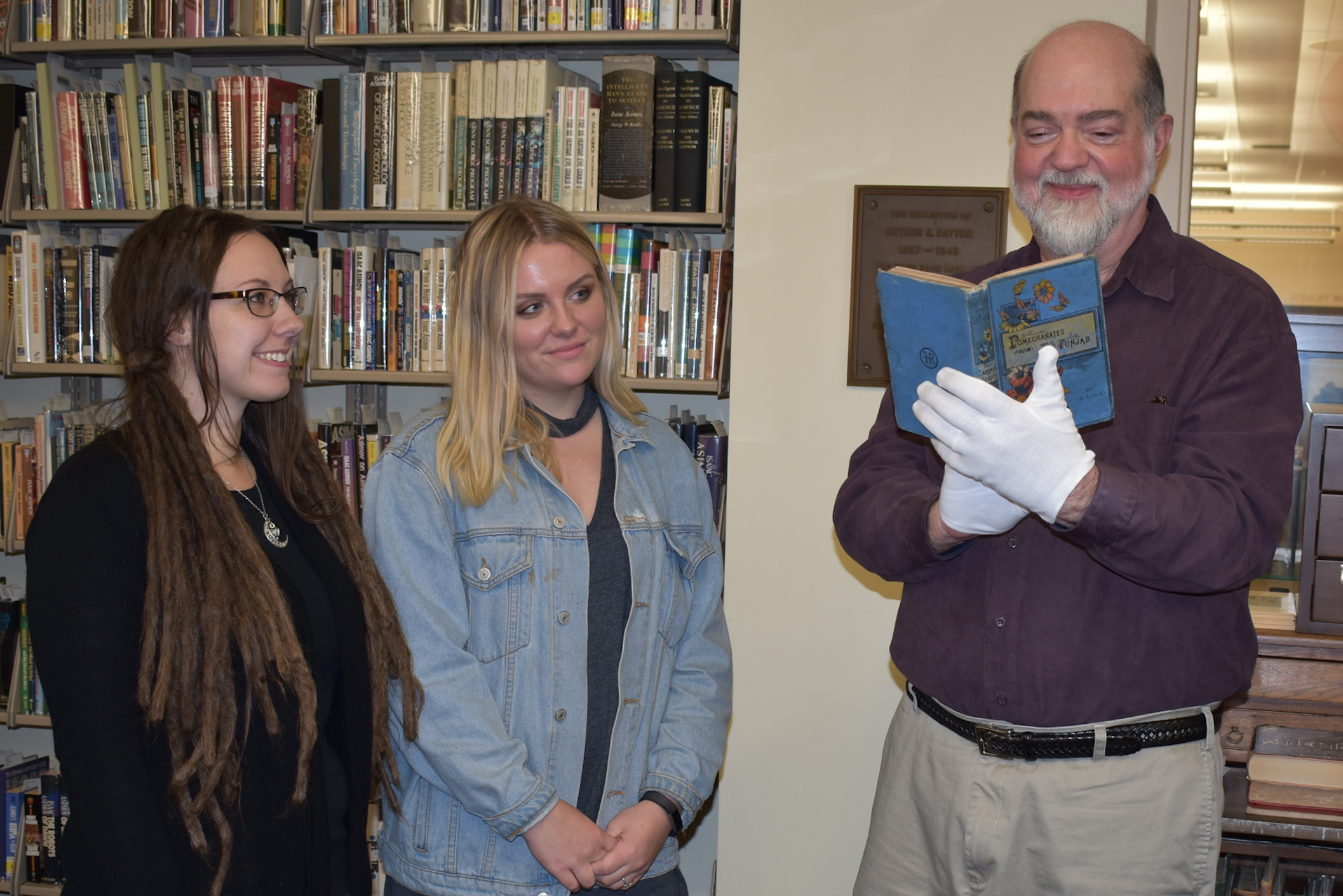Harold Forbes, retired rare books curator, peruses a book dealer Jim Presgraves donated to WVU Libraries in honor of Forbes as library associate Autumn Summers and work study student Jamie Rood look on.