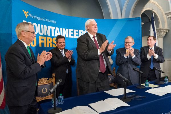 Marshall University President Jerome Gilbert (far left), West Virginia University President Gordon Gee (right), West Virginia School of Osteopathic Medicine President Dr. Michael Adelman (far right) join Governor Jim Justice (center) for signing of HB 2815 (Relating to High Education Governance) at Stewart Hall on the WVU Morgantown Campus April 25, 2017.