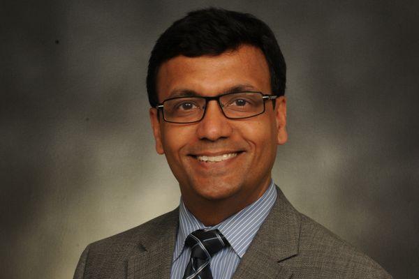 smiling man in suit, tie, glasses