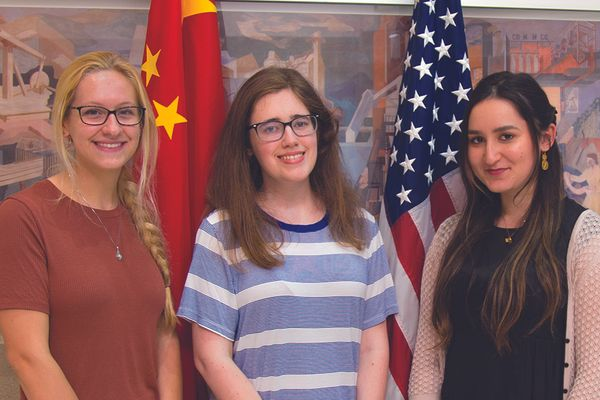 Three young women stand in front of China/American flags
