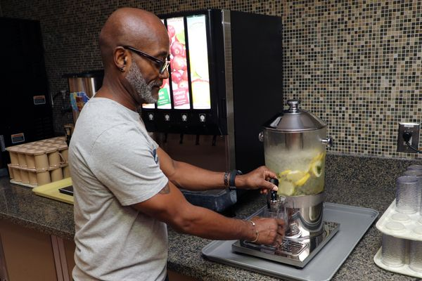 A gentleman with a grey beard and glasses in a grey t-shirt fills his cup with lemon-infused water.