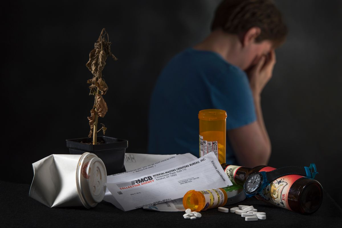 A man sits with his face in hands, his back to a pile of mail and opened pill bottles