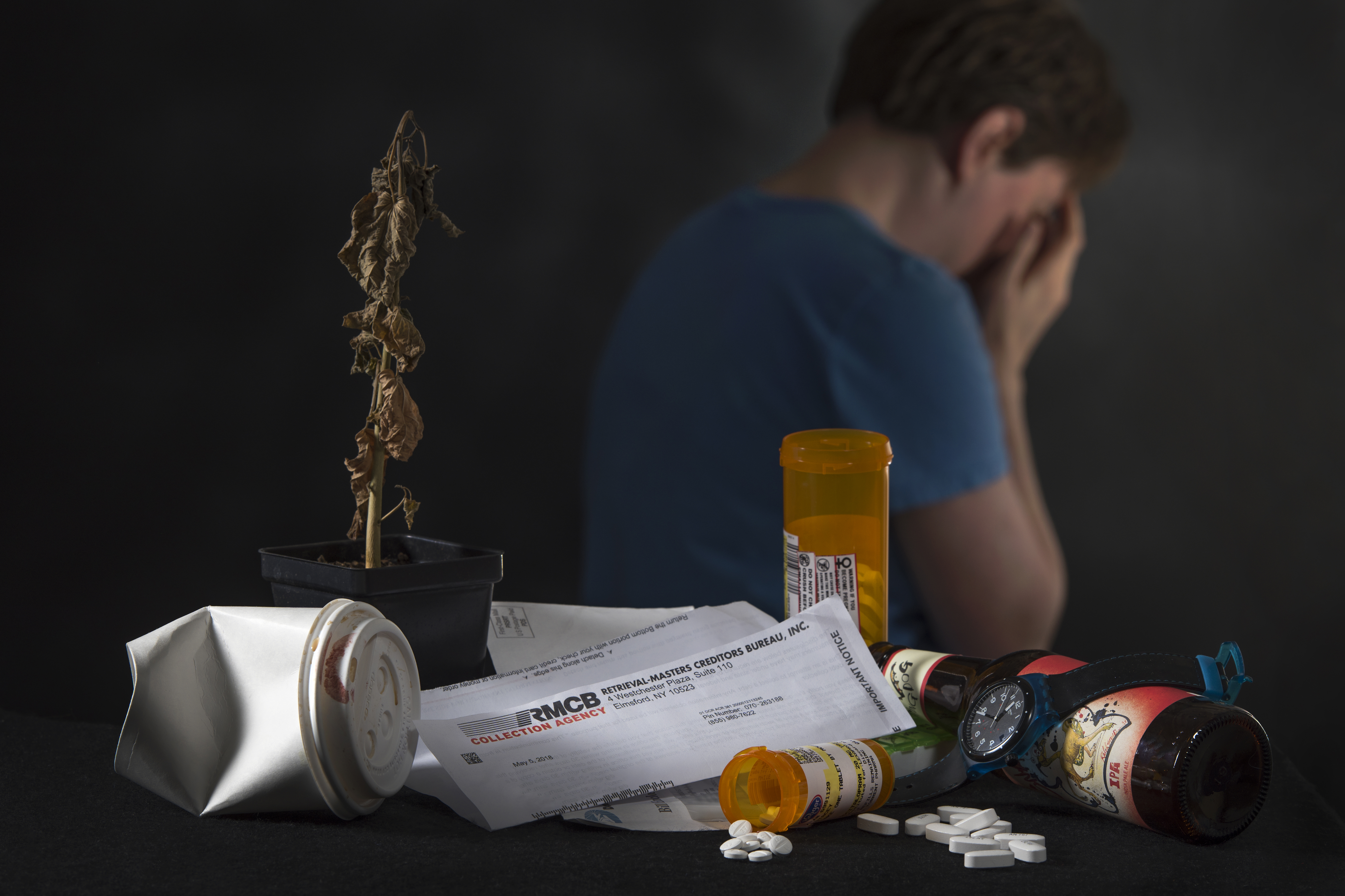 A man sits with his face in hands, his back to a pile of mail and an opened pill bottle