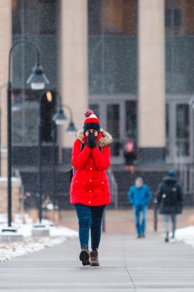 WVU student in red coat covers face with gloved hands to stay warm.