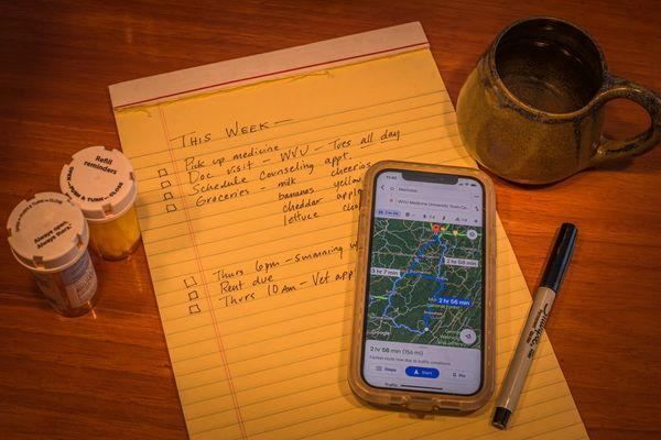 notepad with cellphone map, pen, pill bottles, mug