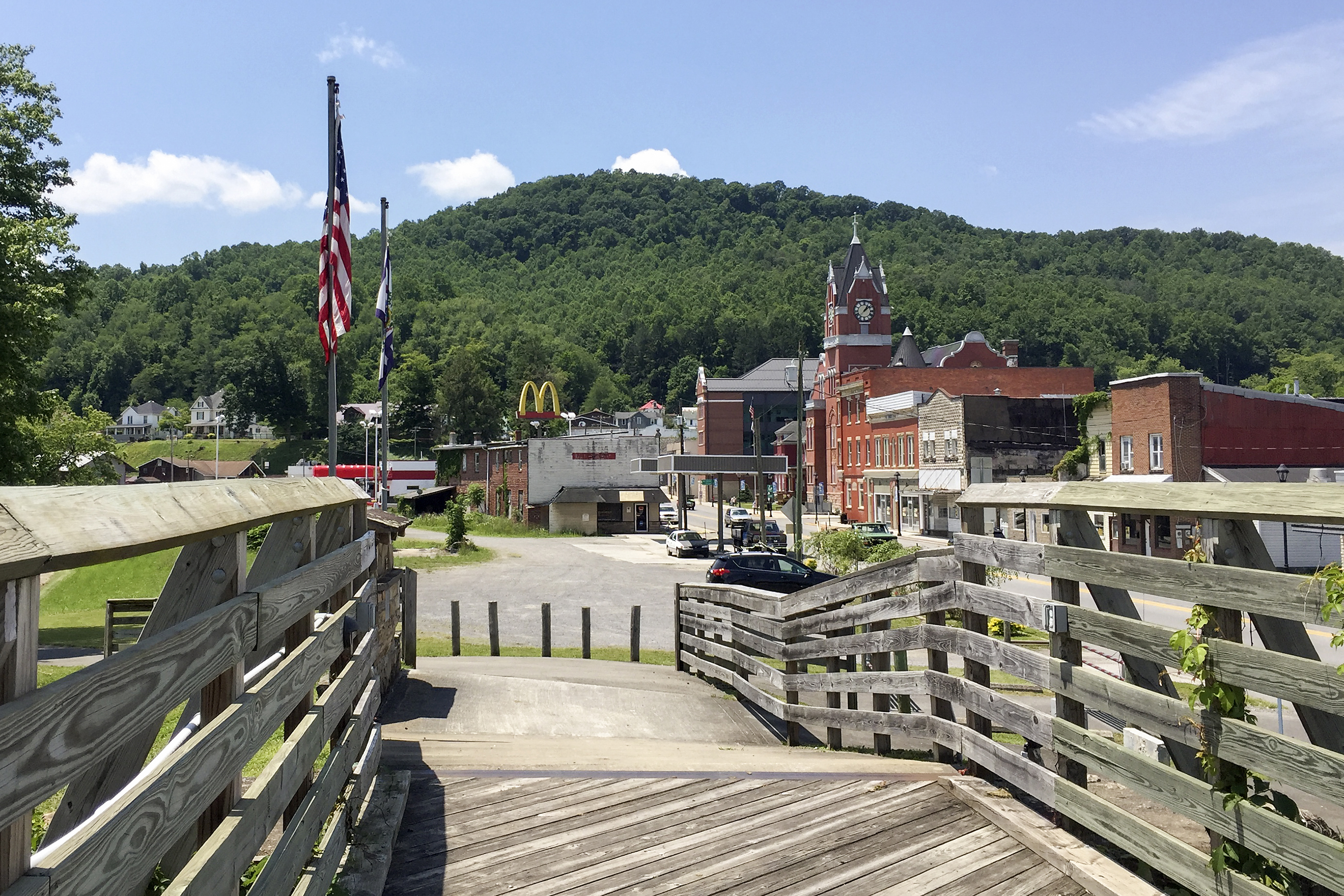 A small town at the foot of a mountain with a boardwalk in the foreground