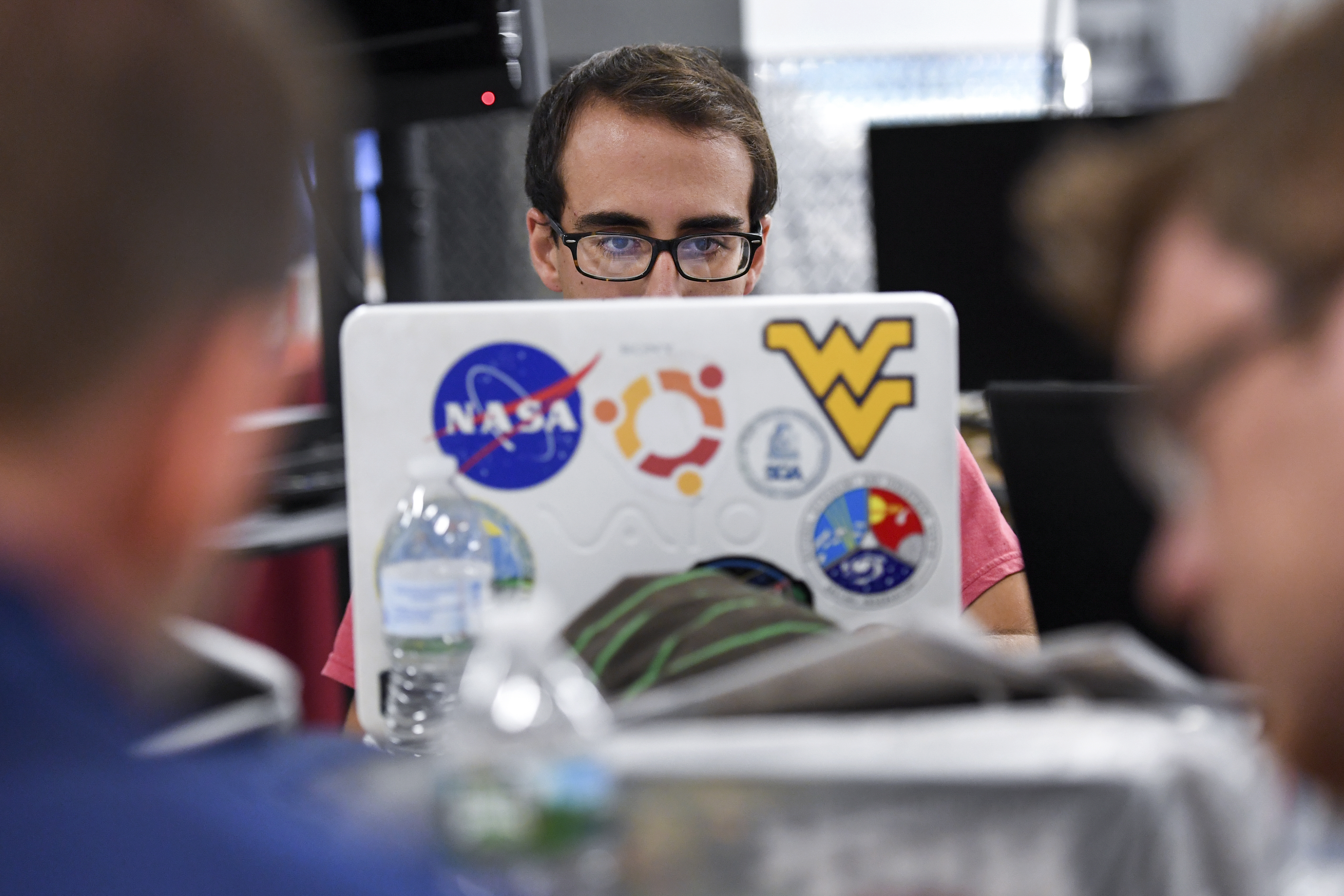 WVU programmer sitting in front of computer.