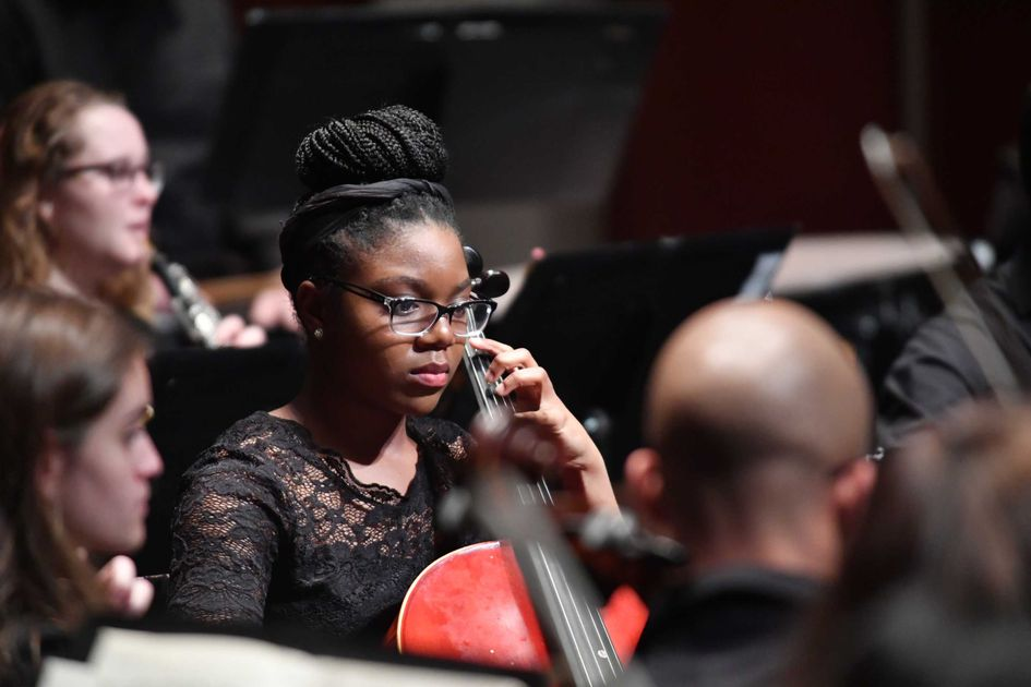 A young woman wearing glasses plays the cello in an orchestra