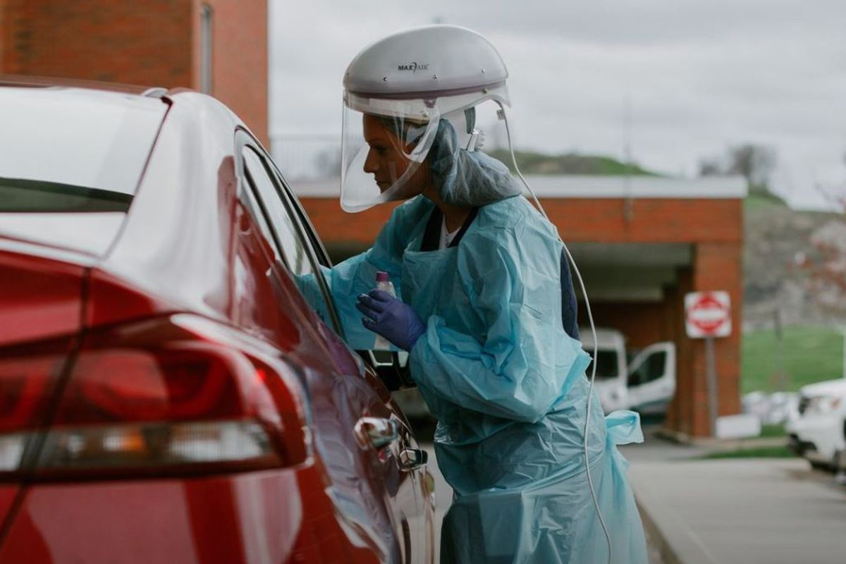 Healthcare worker in suit testing a potential COVID-19 patient in a red car