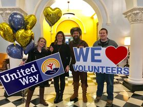 Four people celebrate United Way with balloons, signs and the WVU Mountaineer