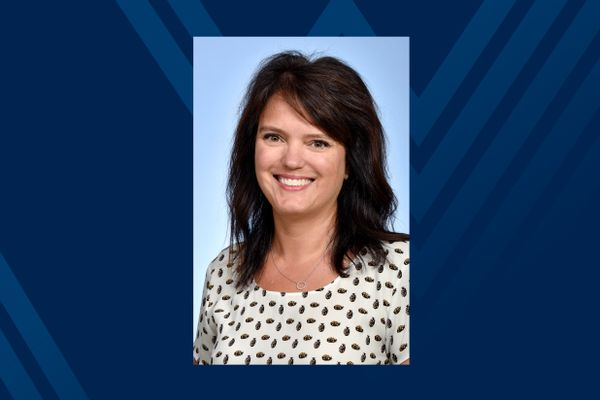 smiling woman with dark hair, print top on blue background