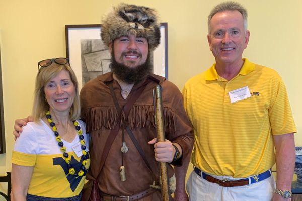 woman, man flank man dressed in buckskins and coonskin cap