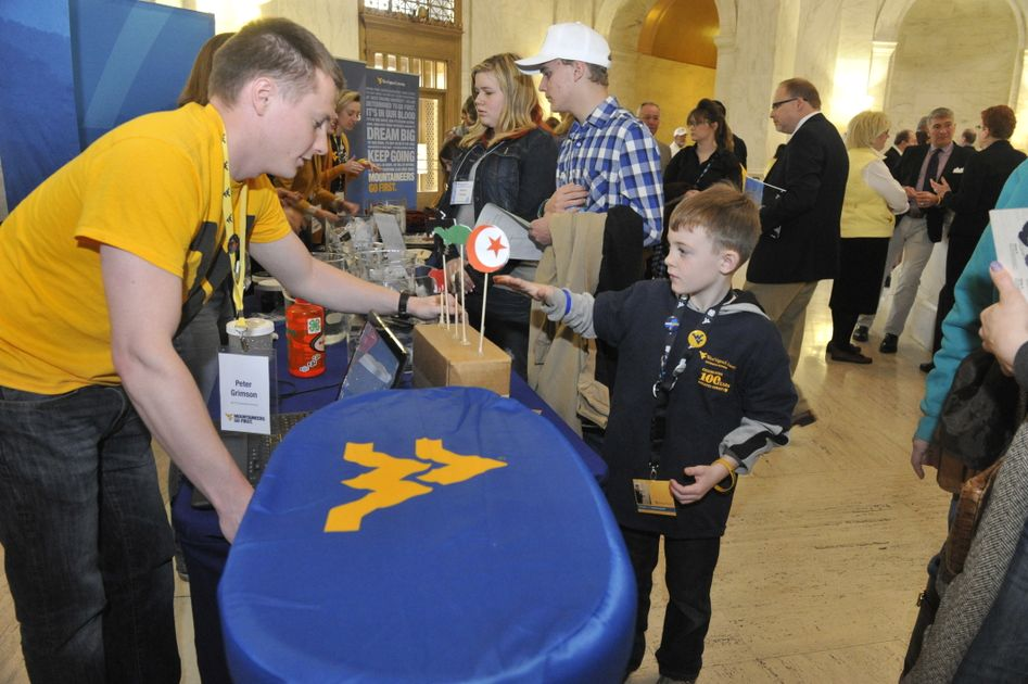 Young man interacts with child at a tabling event.