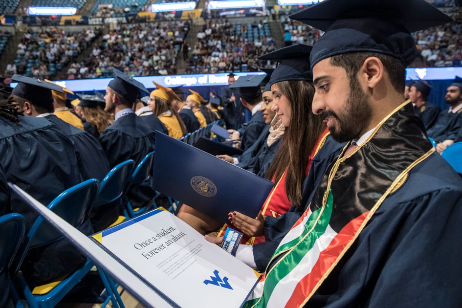 Aziz Aldasem reads his diploma after walking during the College of Business and Economics Commencement in the Coliseum.